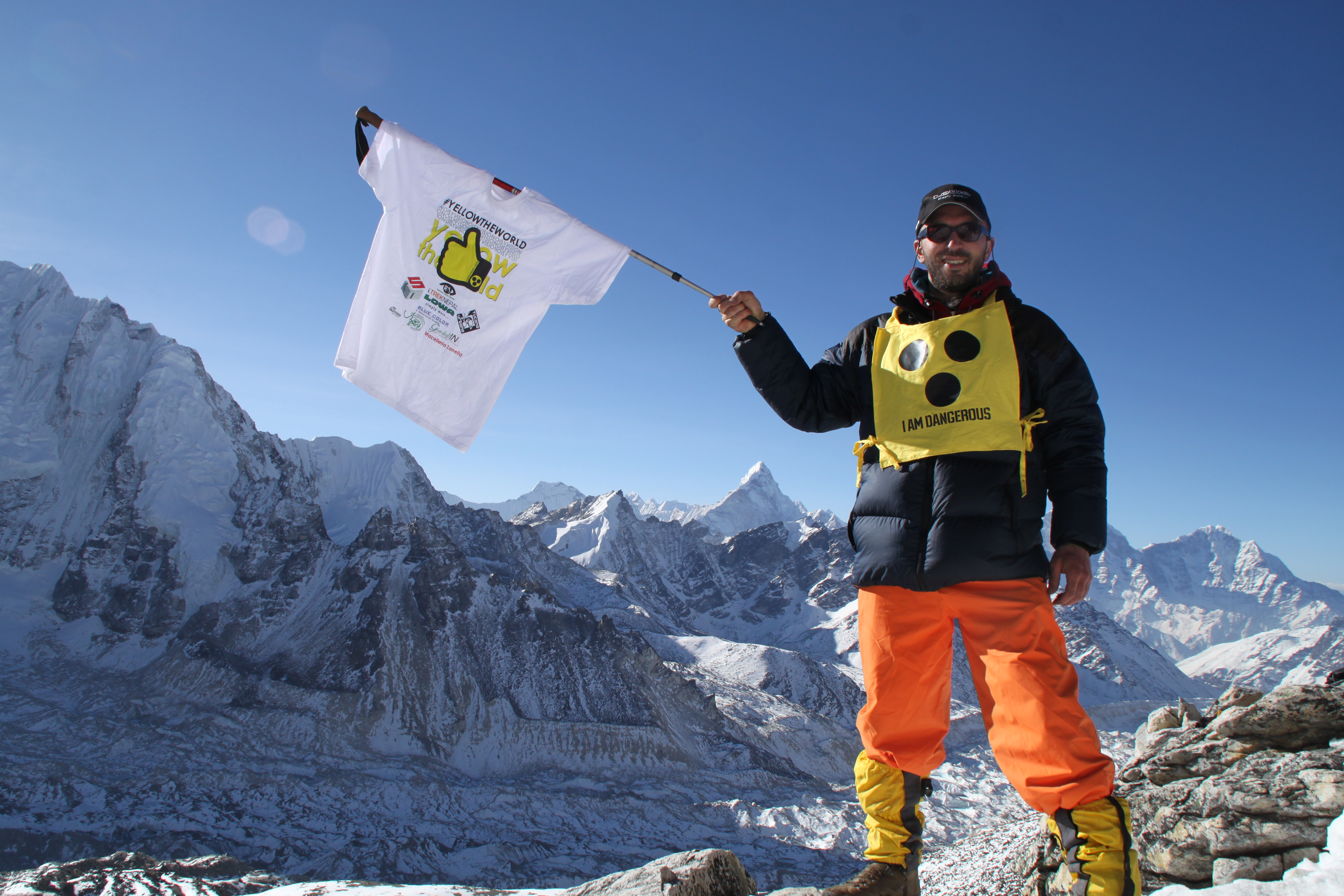 A photo of Dario Sorgato standing on top of a snow covered mountain holding a Yellow the World tee-shirt on a pole