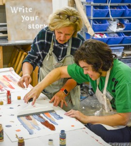 Student and teaching artist paint together using adaptable tools