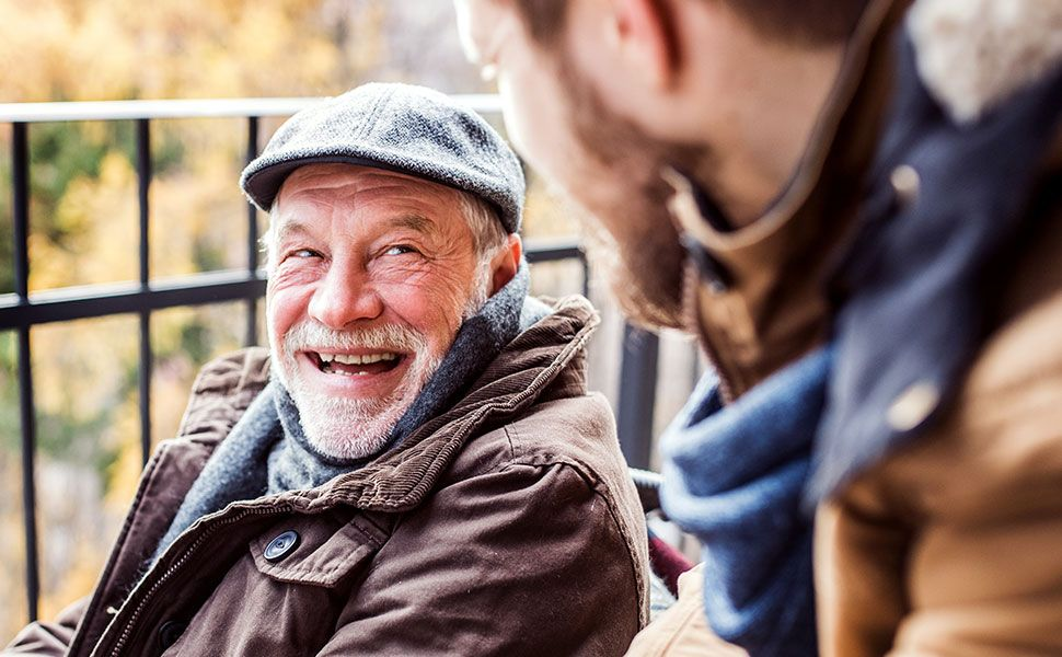 Older man in wheelchair smiling at son who is out of focus and leaning into view