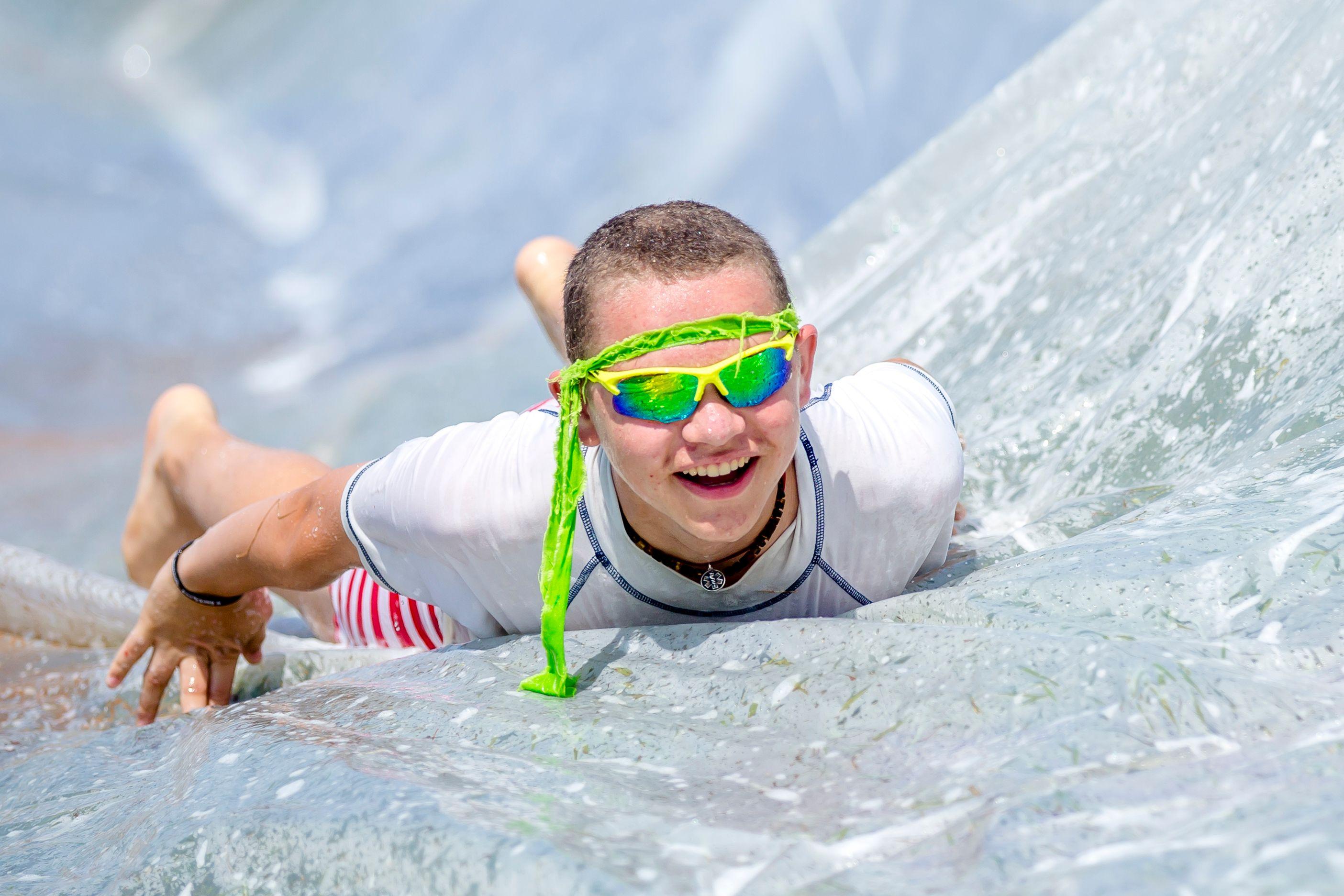 A camper slides down the slip-n-slide.