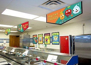 Elementary school café serving line with 3 nutrition education banners hanging above