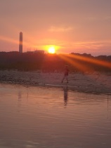This is a picture of a sunset on the beach. A person is walking on the beach, and a tall building is in the distance.
