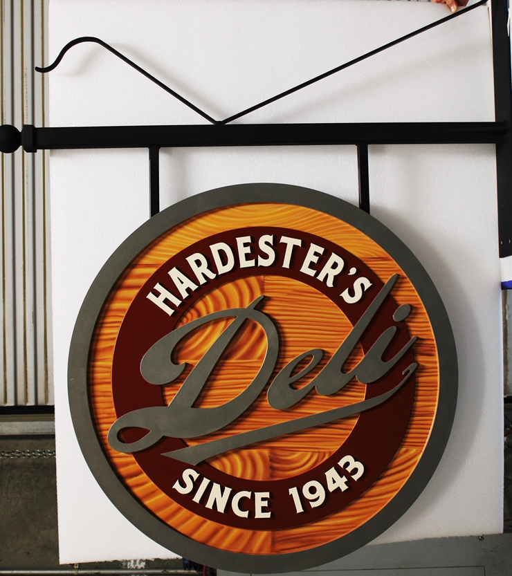 S28163 - Carved Multi-Level High-Density-Urethane (HDU) sign for Hardester's Deli, Painted in a Faux Wood Pattern , mounted Below a Custom Steel Scroll Bracket