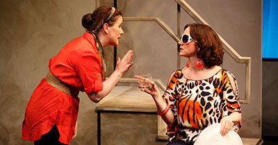 MERCHANT OF VENICE - 2012. Mary is leaning over, wearing an orange dress, and her hands in Pamela's view. Pamela, in a cheetah print blouse, is sitting on a chair, facing Mary. Pamela is pointing her finger at Mary. They are having a conversation.