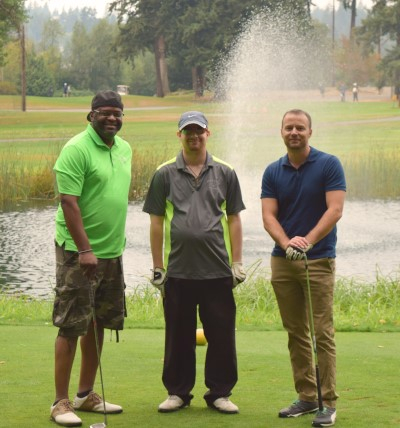 Reggie, Preston, and Scott pose in front of fountain with golf clubs