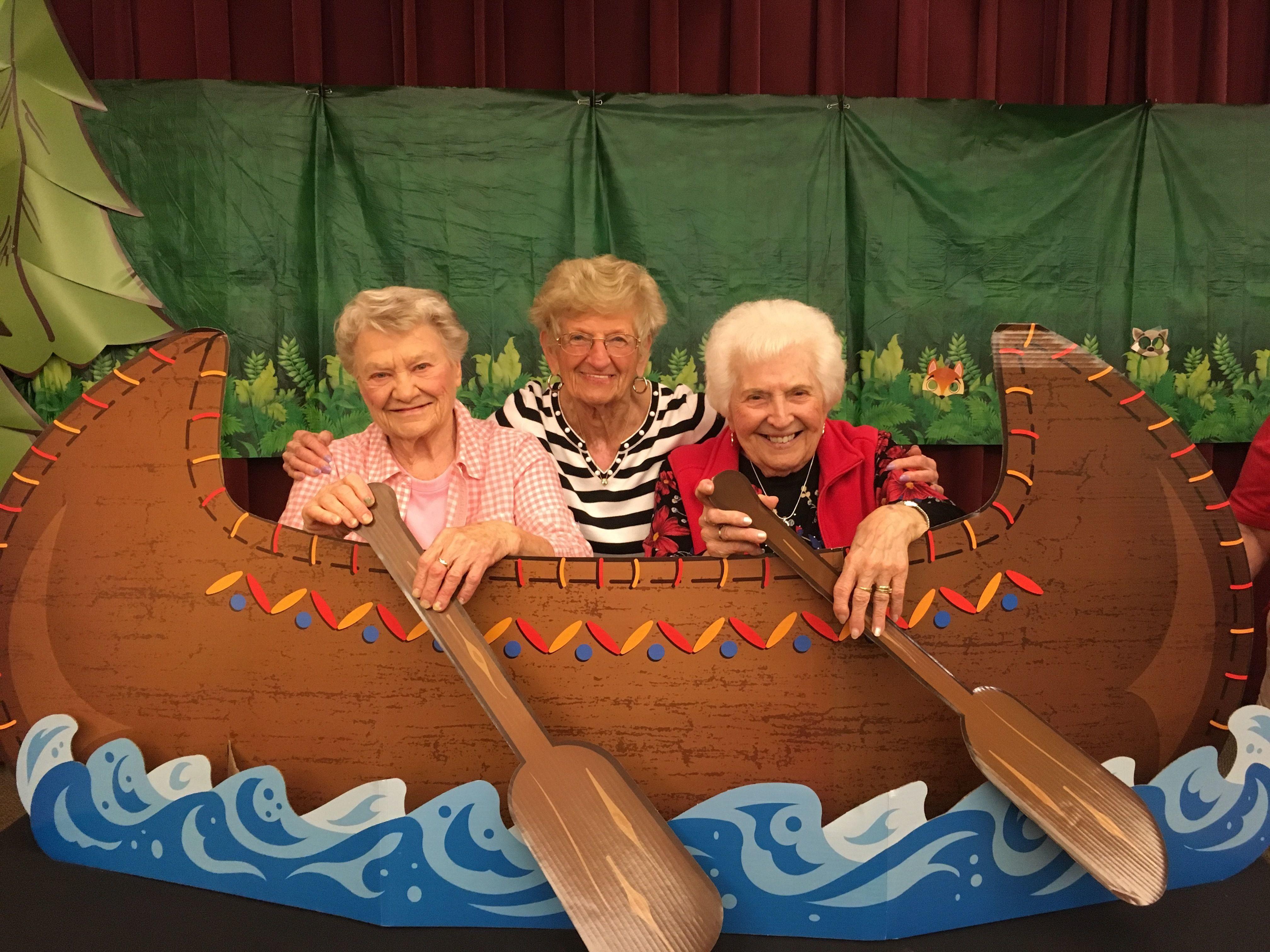 Three Coburg Village residents rowing a fake canoe