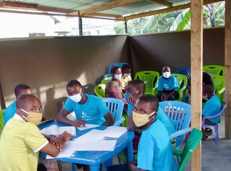 Students sitting around table studying and wearing masks.