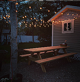 Patio porch with tea lights hanging from birchwood posts