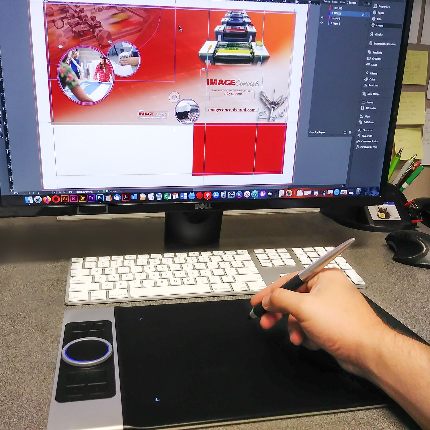 Graphic designer using pen tablet and computer for print layout and design