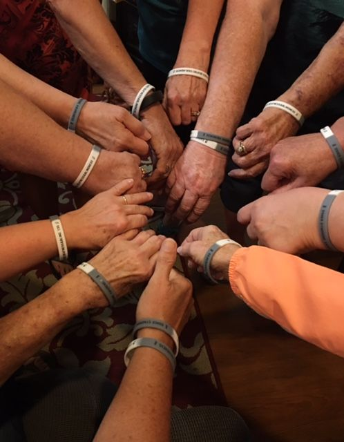 Group of arms wearing bracelets.