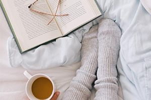 An open book on a cozy bed showing blankets and warm socks from Goodwill.