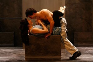ROMEO AND JULIET - 2008. Emily Young is wearing a light blue blouse and holding Gregg Mozgala's necklace. She is laying on a dark box while Gregg is on top of her. He's shirtless and he's wearing khakis pants. They are talking.