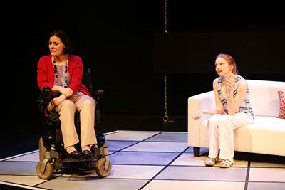 I DARE YOU by Neil La Bute (L to R): Ann Marie Morelli is sitting in a power wheelchair, wearing a red jacket and white pants, looking to her right. Samantha Debicki is sitting on a white couch, wearing a light blue top and white pants.