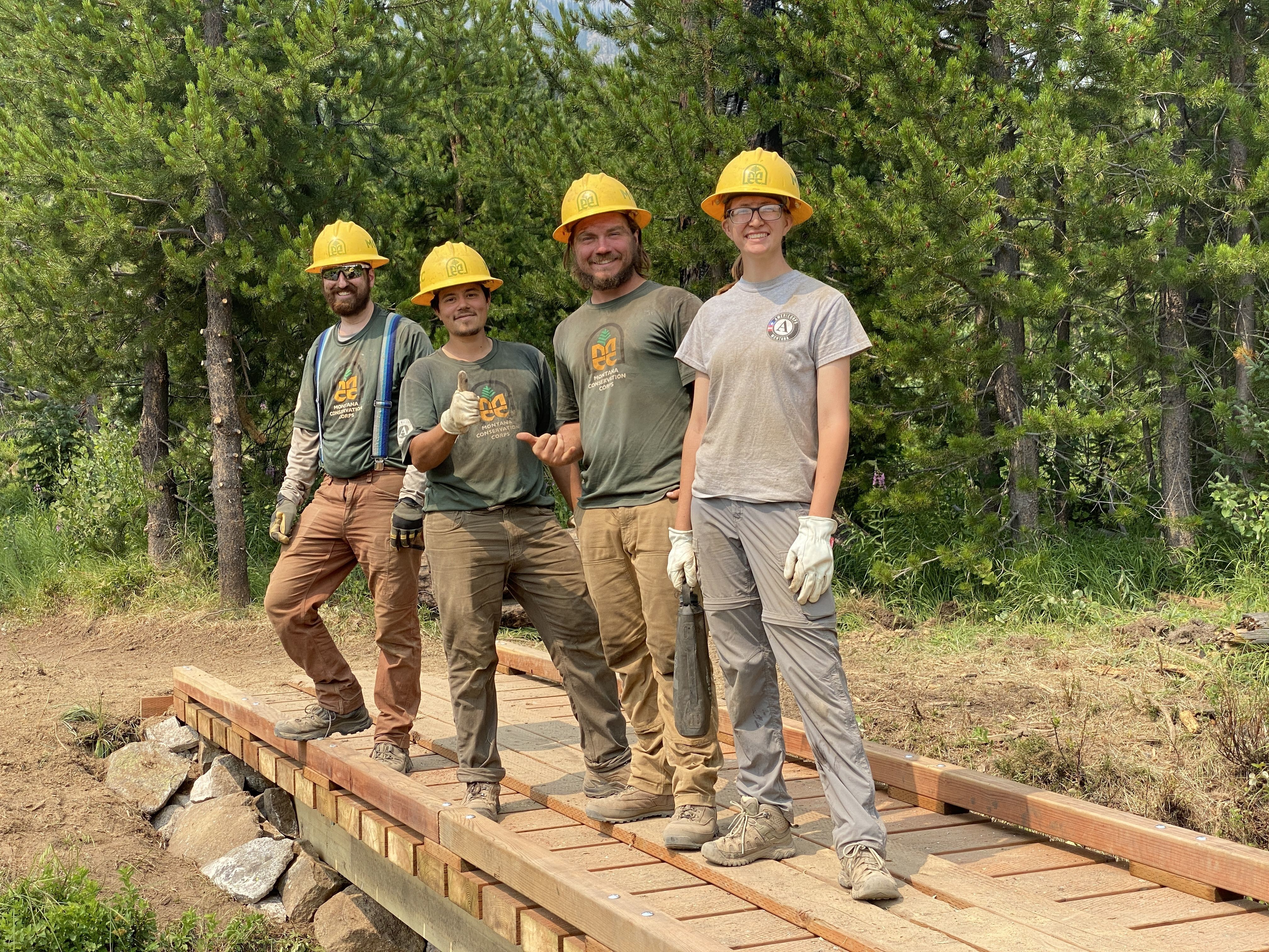 A crew stands on a bridge that they just repaired