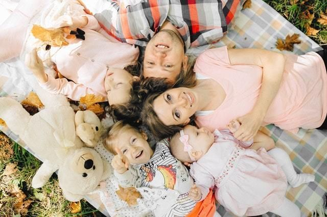 Family laying down on blanket together