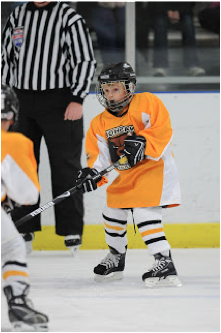 This is a picture of Jack (the blogger's son) playing hockey. He's holding his hockey stick out in front of him and wearing an orange uniform.