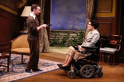 (L to R): Christopher Imbrosciano is standing, wearing a brown sweater with brown pants, holding a handgun aiming it at Ann Marie Morelli. Ann Marie is sitting in her power wheelchair, wearing a skirt and white top. They are arguing in the living room.