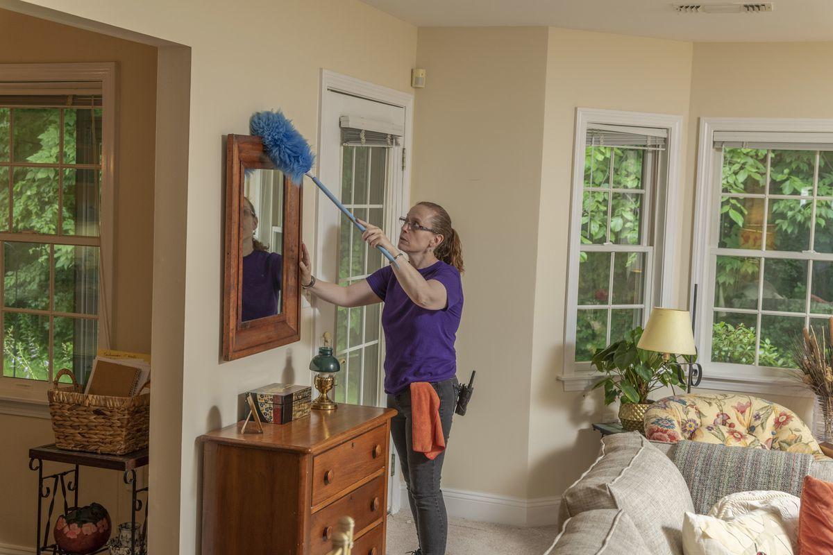 Housekeeper dusting a mirror