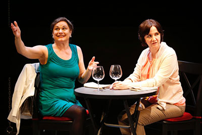 MURDER by Bekah Brunstetter (L to R) Anita is wearing a teal dress with her hands in the air & Pamela is wearing a white sweater and she's hunched over a dinner table with two empty wine glasses. Pamela has a disgusted look on her face.