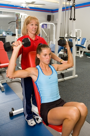 Photo of a PTP personal fitness trainer assisting a client with incline dumbell press exercises