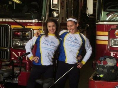 Rebecca and Caroline posing and smiling in front of firetrucks