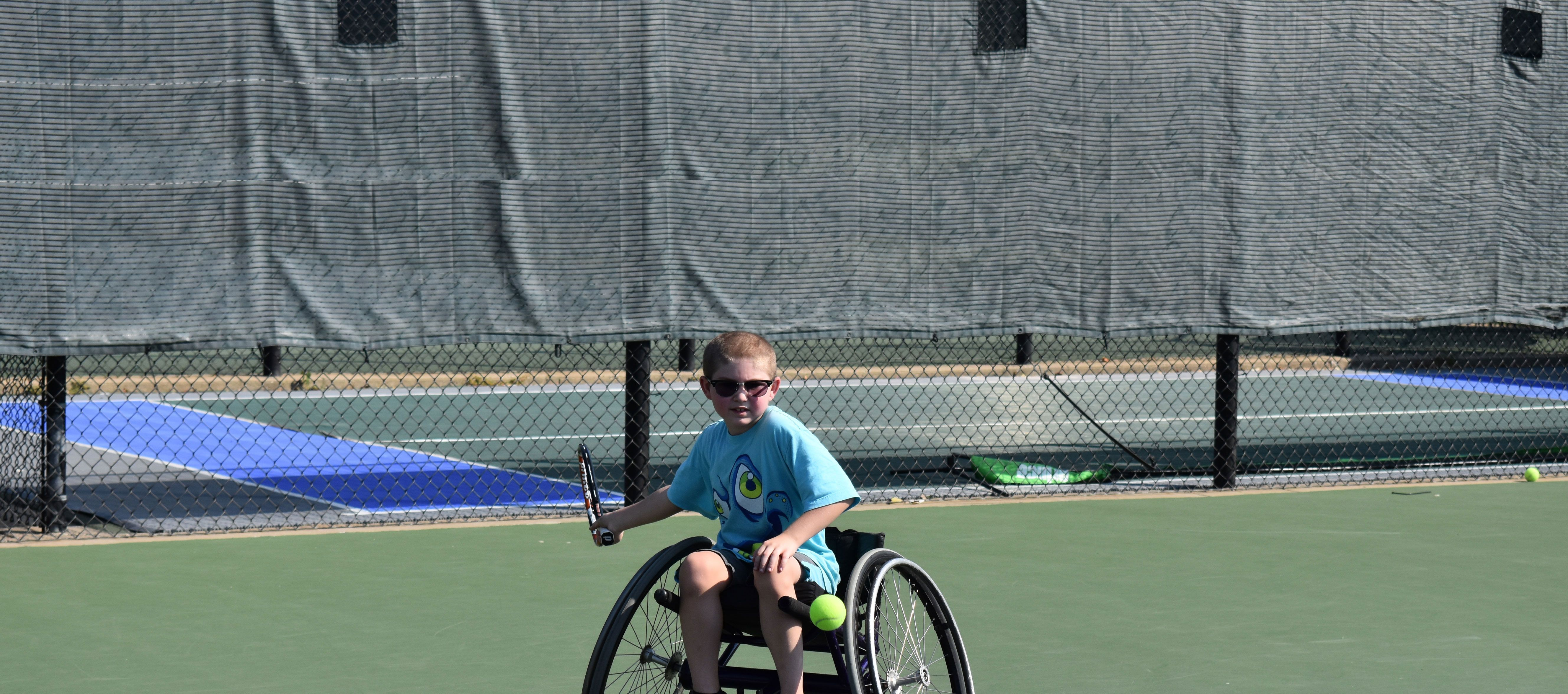 Young boy in wheelchair playing tennis outside