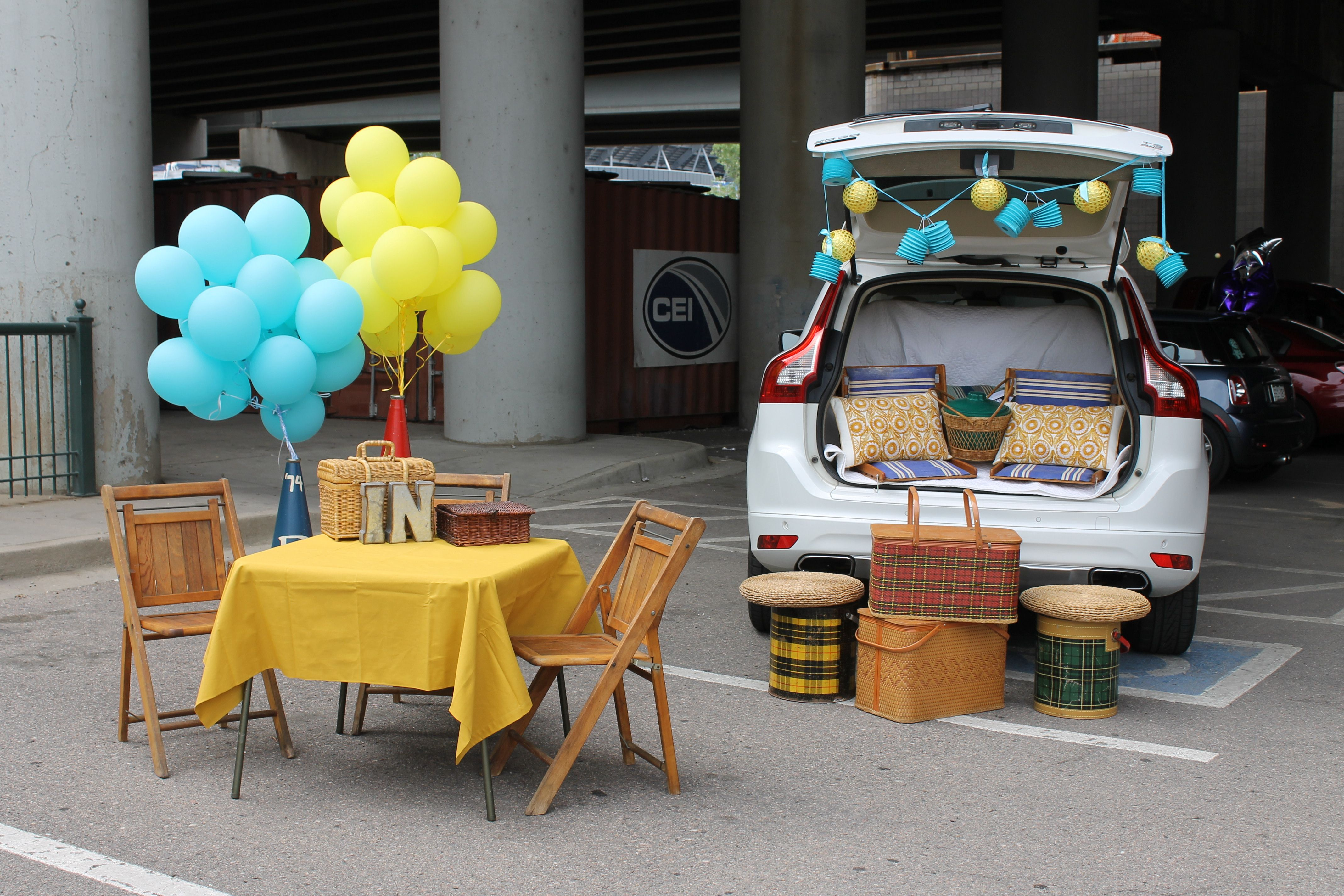 Back of car is open and picnic table with yellow cloth and balloons sits next to car