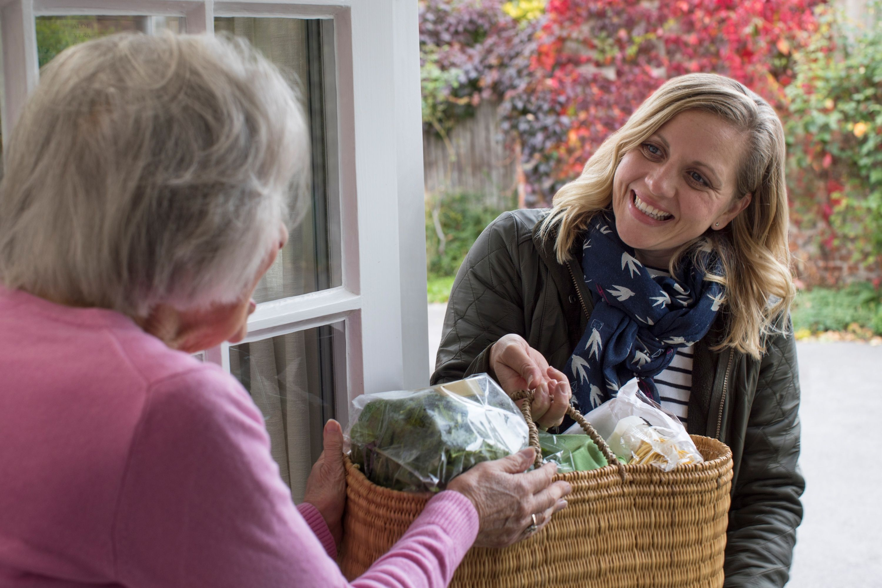 Middle aged woman bringing groceries to older female neighbor, smiling and standing at the front door
