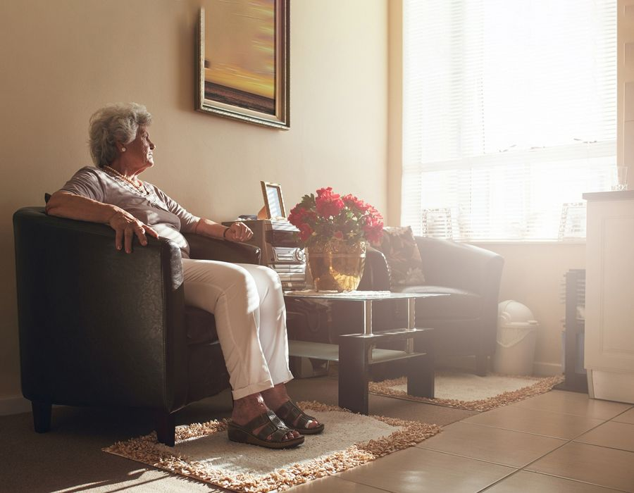Older woman sitting isolated in her home, looking out the window solemnly