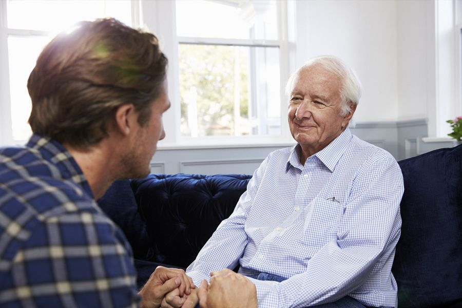 Older man smiling gently as he sits on his couch. A young man sits across from him and they're clasping hands.