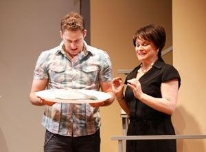 (L to R): Terry Small is standing and holding a plate. He is looking down at the plate and Anita Hollander is standing next to him and holding her hands up while she is speaking to Terry.
