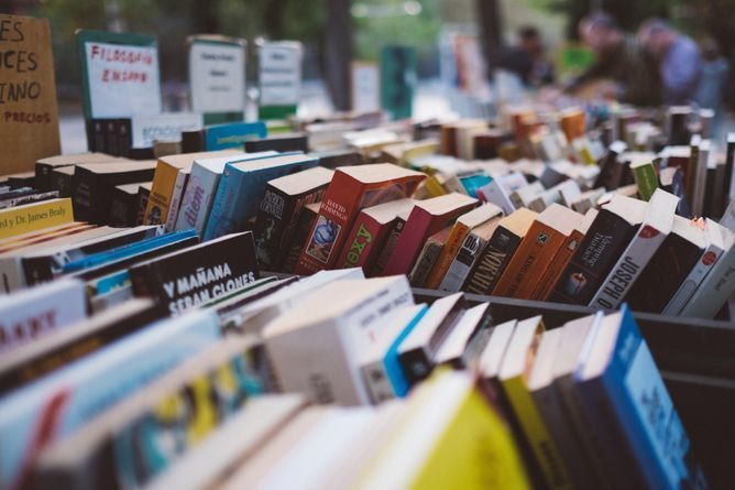 Photograph of a book sale table with books separated into boxes by genre.