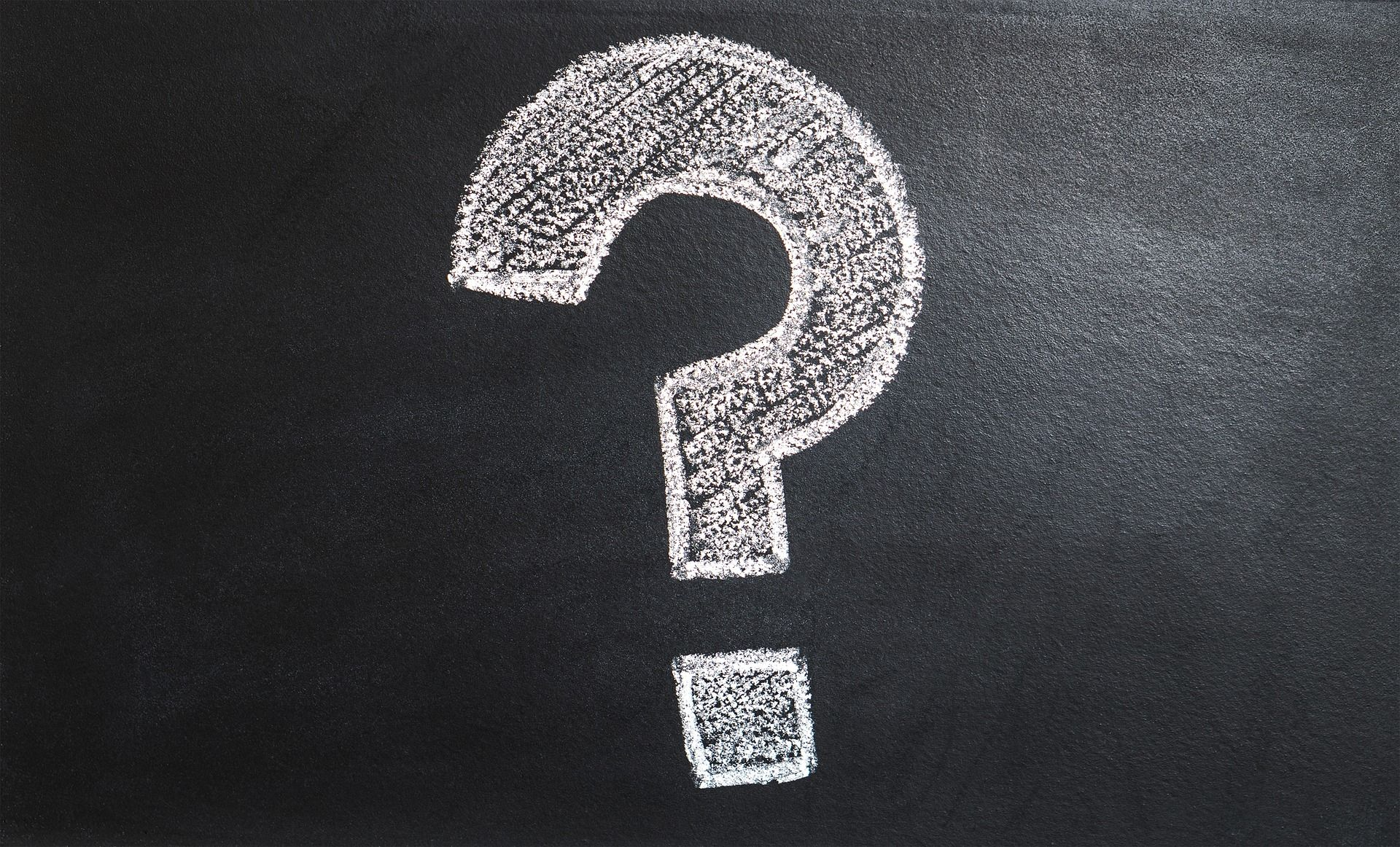 Large question mark drawn in white chalk on a black chalkboard