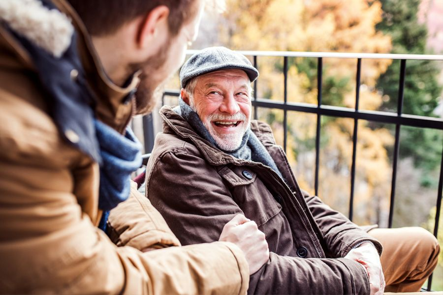 Older man sitting in wheelchair on a balcony, smiling at his son who is out of focus