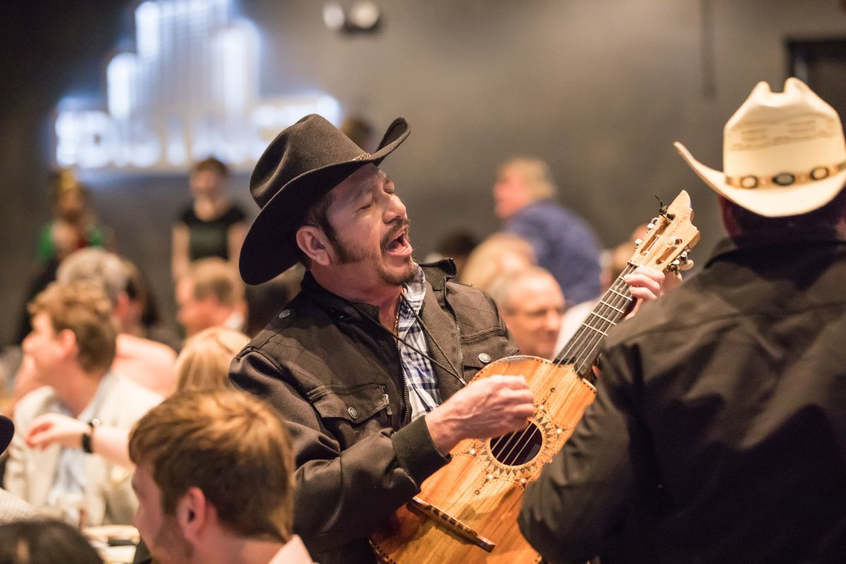 Man playing an instrument among the tables of guests