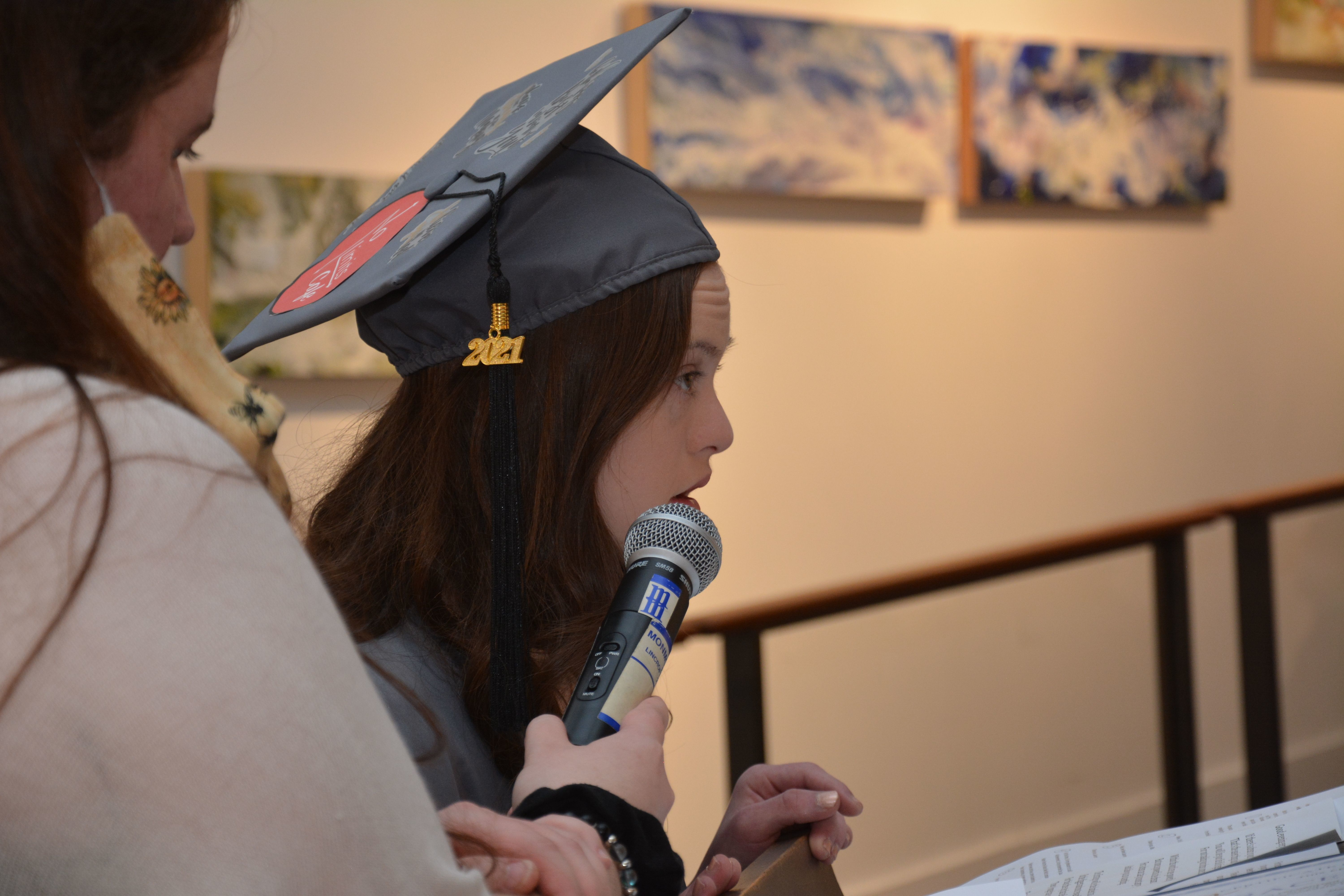 A female student from the KACH program wearing a graduation cap with a 2021 tag.