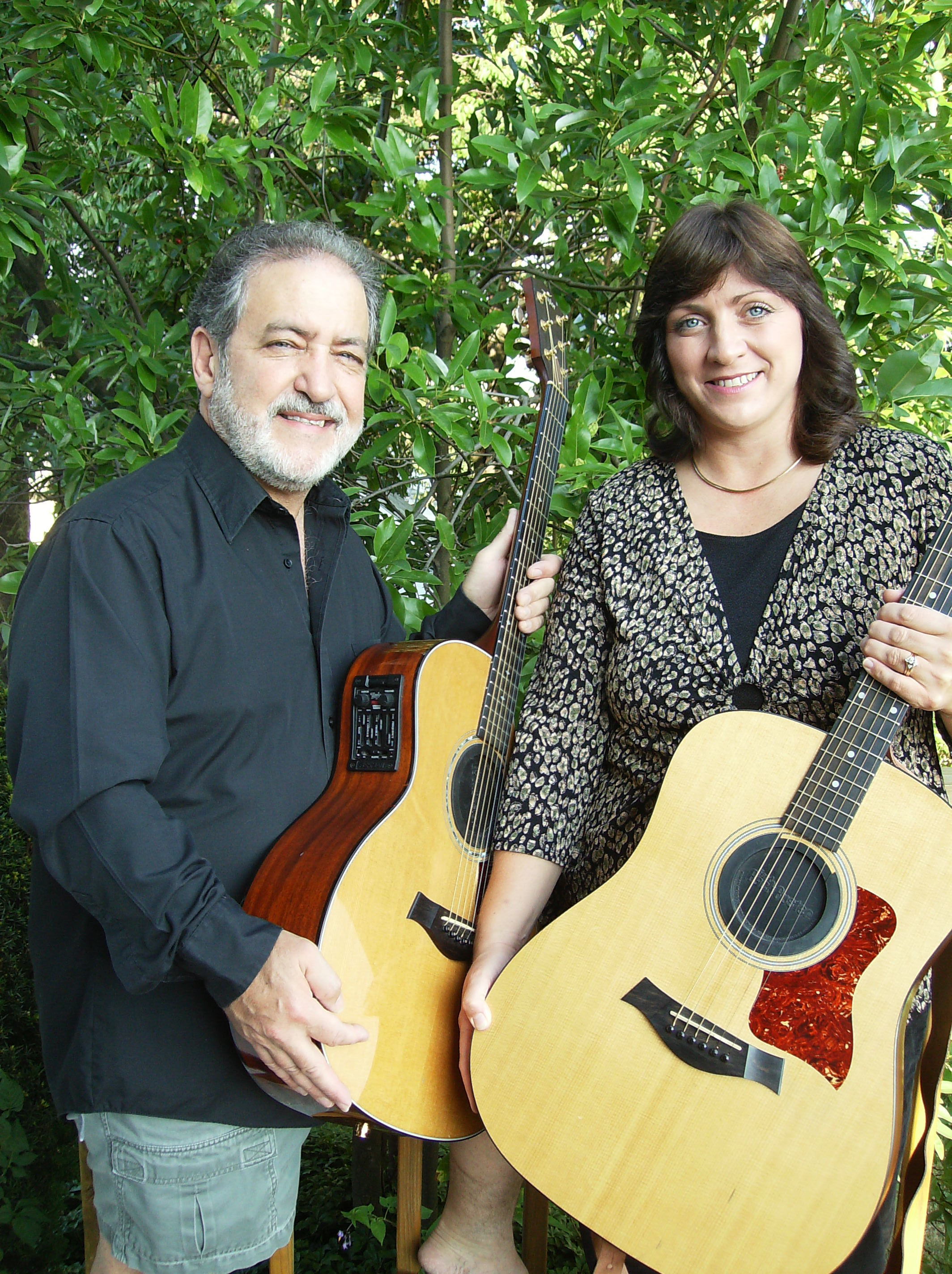 A man and woman posing with acoustic guitars