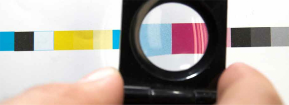 Image of a magnifying glass being used to inspect the quality of a print, made by Colorprint in Burlingame, CA