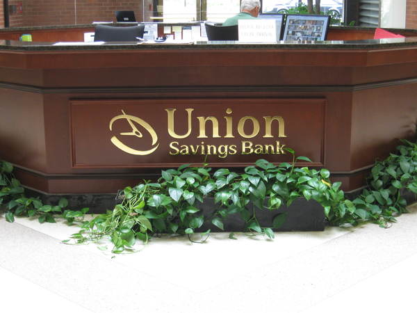 "Interior Reception Area Lobby Sign, 1/4"" Polished Brass Letters on Reception Desk"