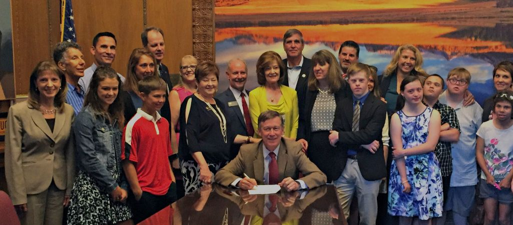 Group of parents and students stand around governor who is signing a bill