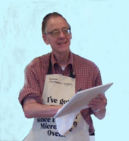 John T. Storz cooking in apron