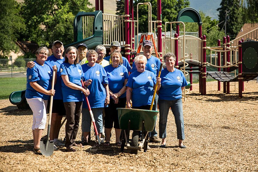 Smiling male and female volunteers wearing their Senior Corps t-shirts at a playground. They're holding shovels and standing in front of a wheelbarrow.