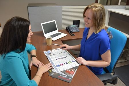 Two women sitting at desk, discussing a catalog.