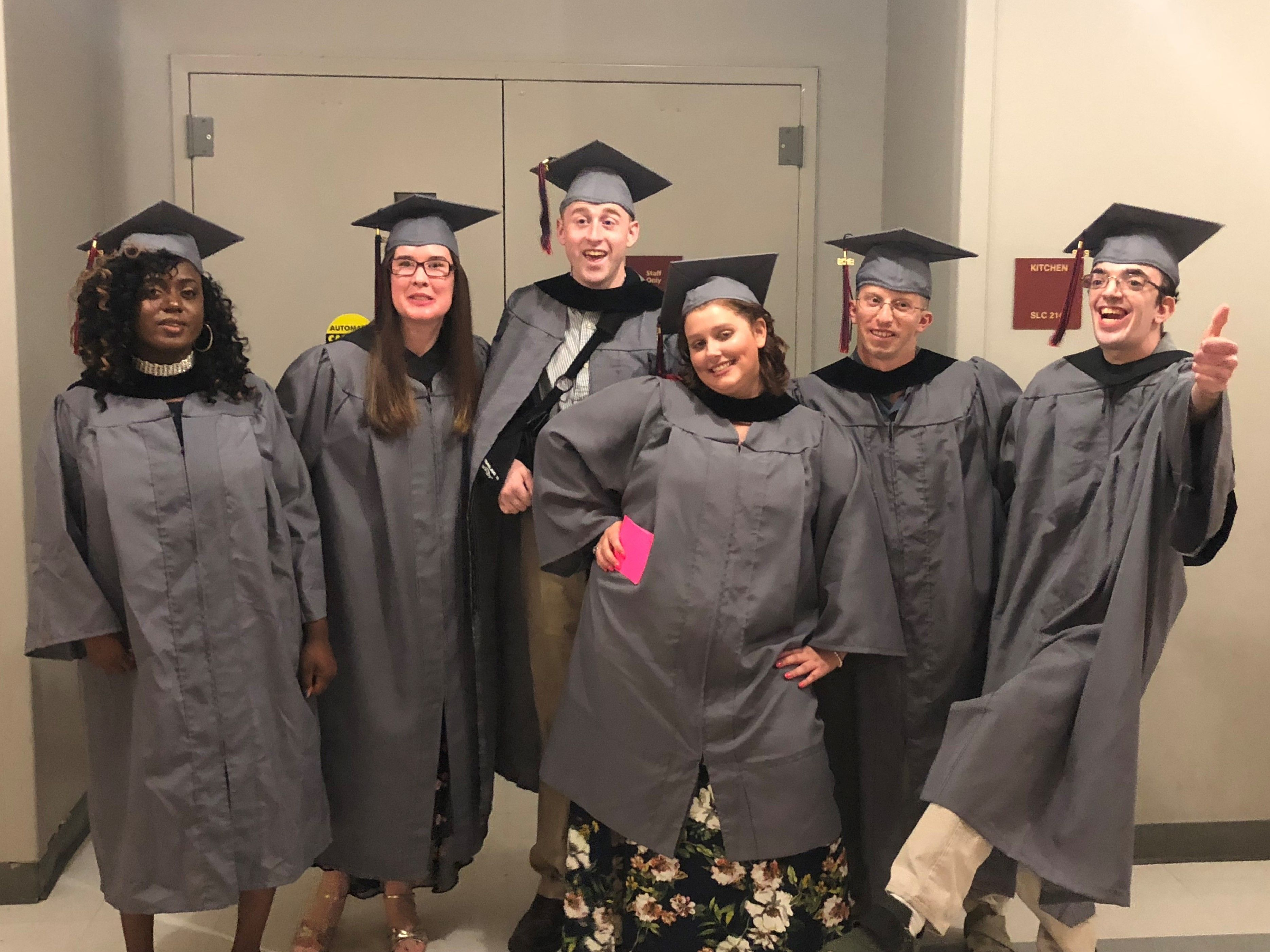 2019 Kach Graduates stand in cap and gown on graduation day.