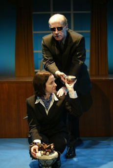 OEDPIUS - 2005. Pamela is wearing a suit, a blue scarf and kneeling holding a tray with her head turned listening to J. Martin. He's wearing dark glasses, sitting behind Pamela on the edge of a window. He's wearing a suit, trying to grab the tray.