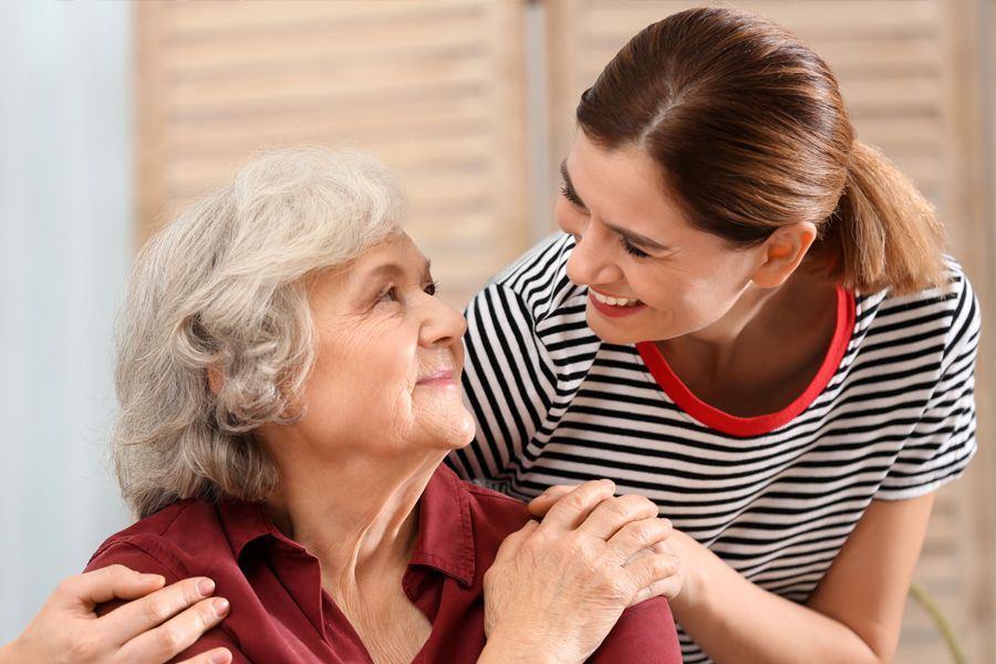 Older woman sitting in her room, gently smiling up at a young woman who's hand in on her shoulder.