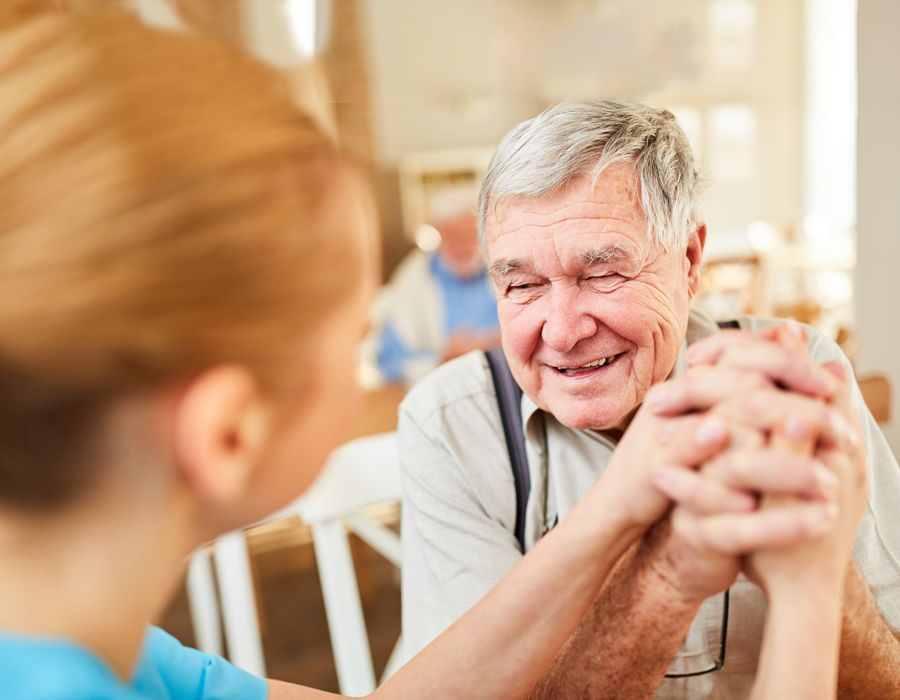 Smiling older man sitting with his caregiver in an assisted living home. They're clasping hands.