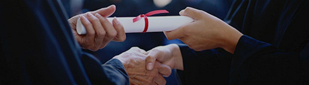 Two people shake hands while holding a college diploma