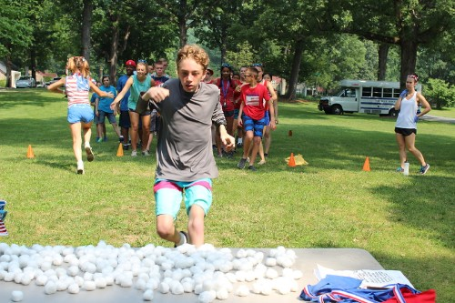 A camper runs in a relay race challenge.