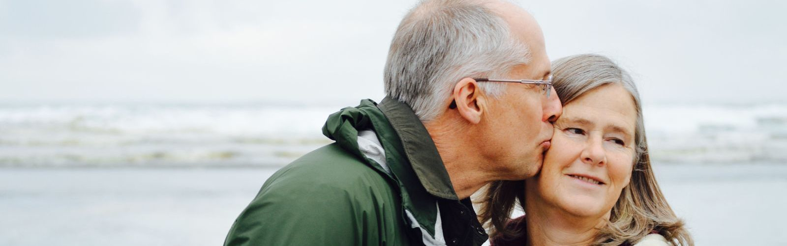 stock photo of man kissing woman at the beach